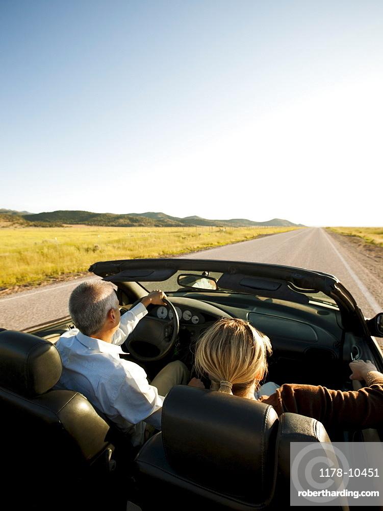USA, Utah, Kanosh, Mad-adult couple driving through desert plains in convertible car