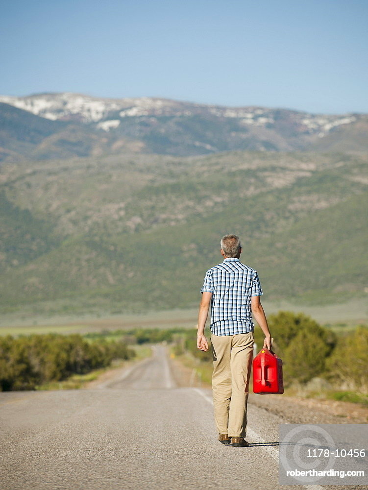 USA, Utah, Kanosh, Mid adult man carrying empty canister along empty road