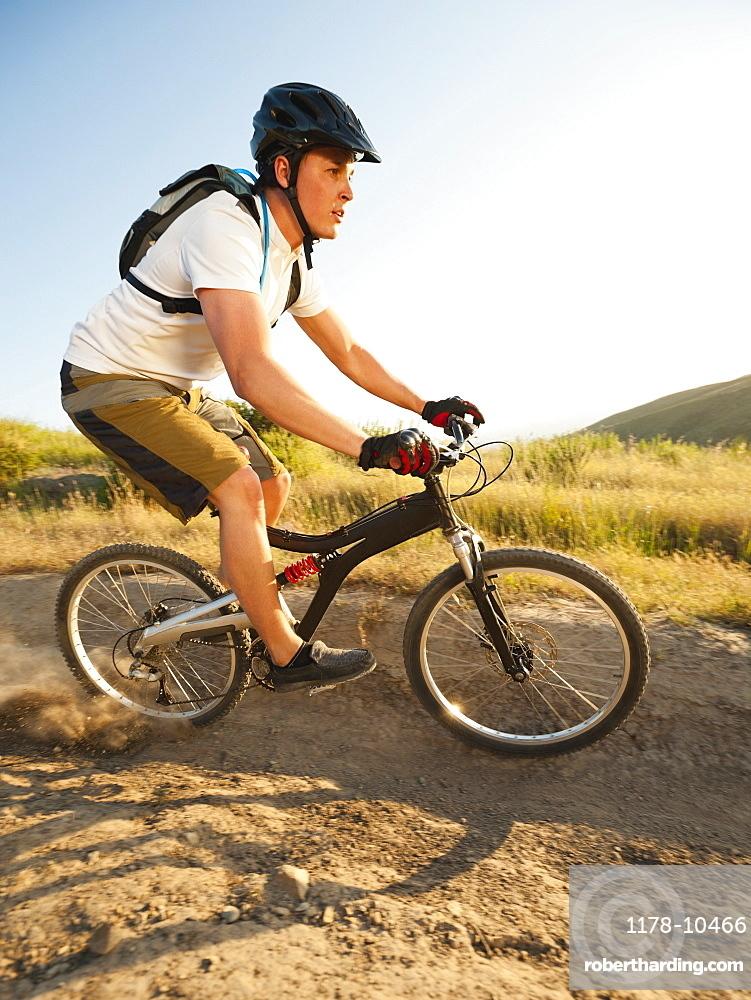 USA, California, Laguna Beach, Man cycling down hill