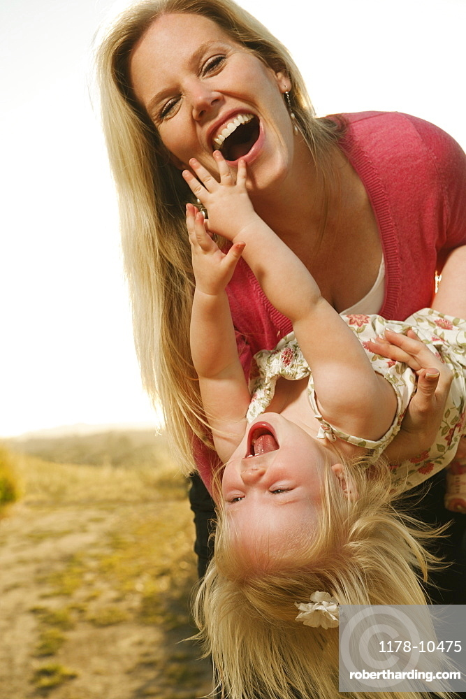 Mother playing with daughter (12-17 months) and laughing