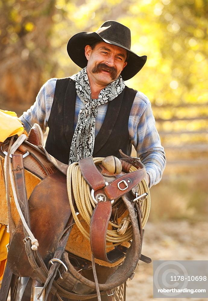 Cowboy holding saddle