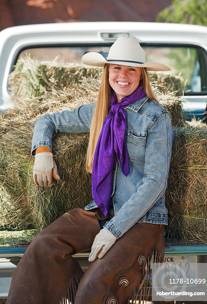 Cowgirl sitting on back of truck