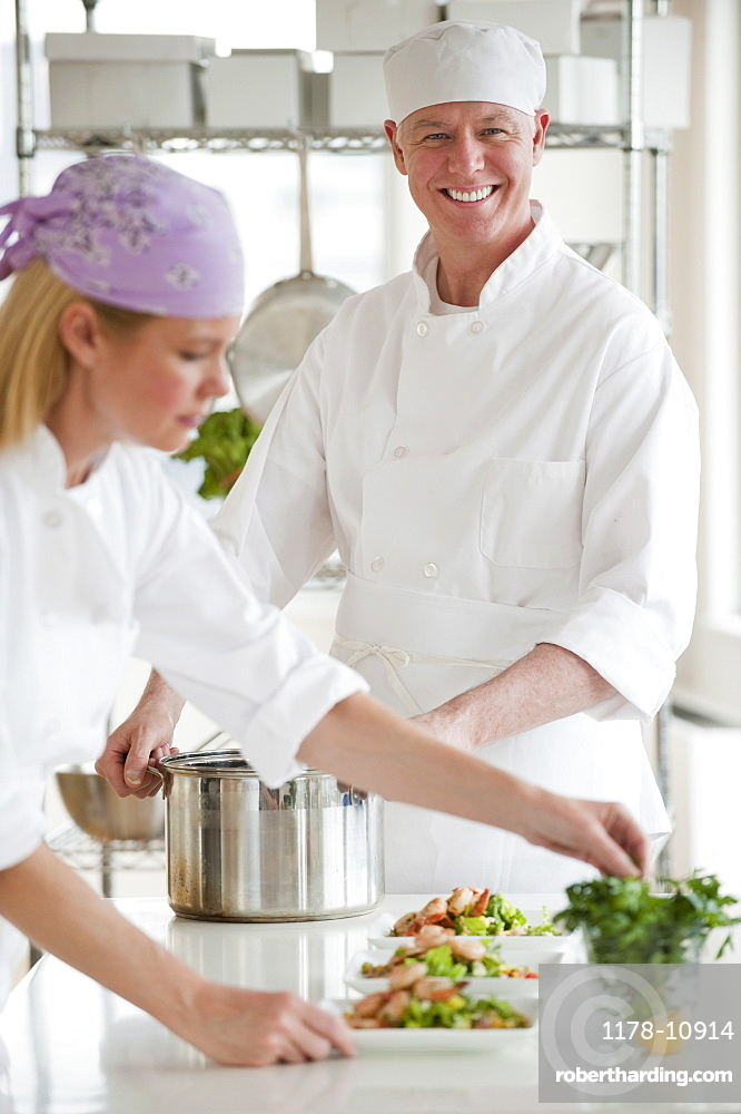 Chefs making salad in a kitchen