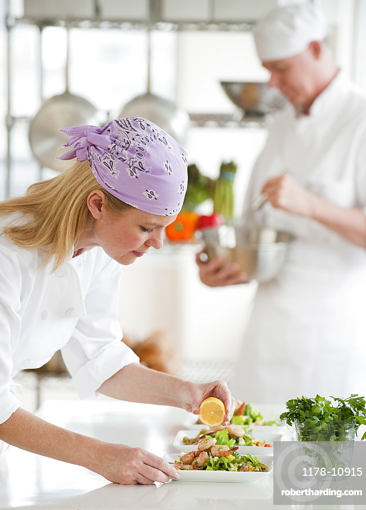 Chefs making salad in a kitchen