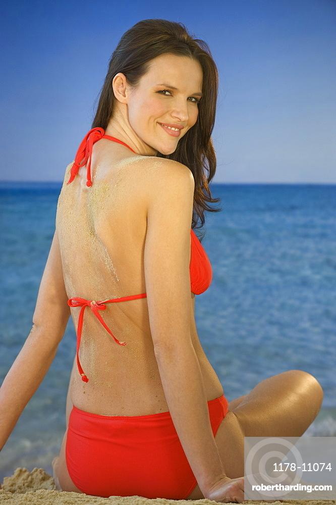 Portrait of woman in bikini sitting on beach