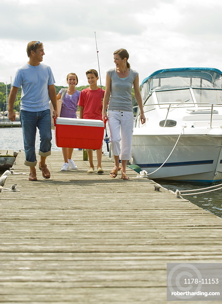 Family walking on boat dock with cooler