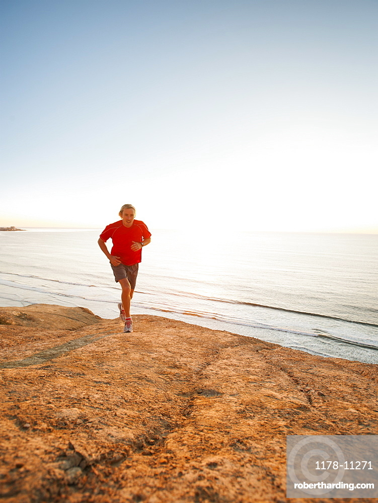 USA, California, San Diego, Man jogging along sea coast