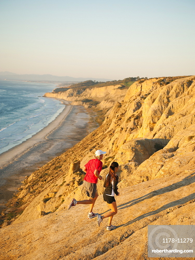 USA, California, San Diego, Man and woman jogging along sea coast