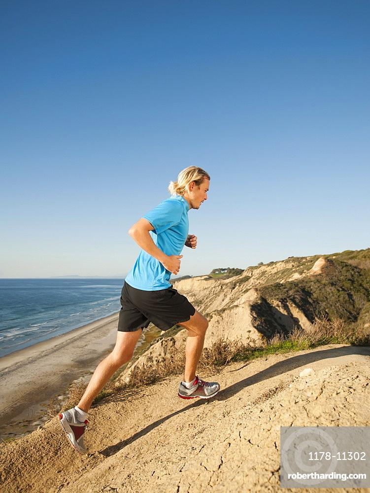 USA, California, San Diego, Man jogging along sea coast