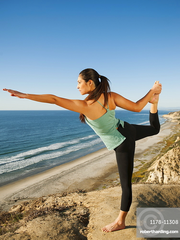 USA, California, San Diego, Woman practicing yoga on beach