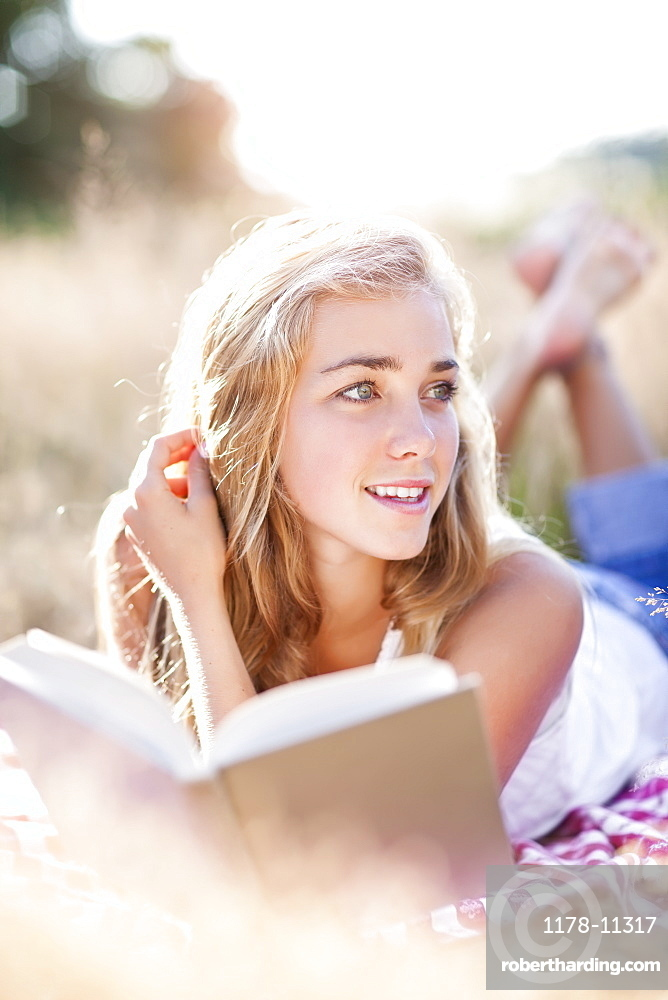 Teenage girl (16-17) taking break from reading book outdoors
