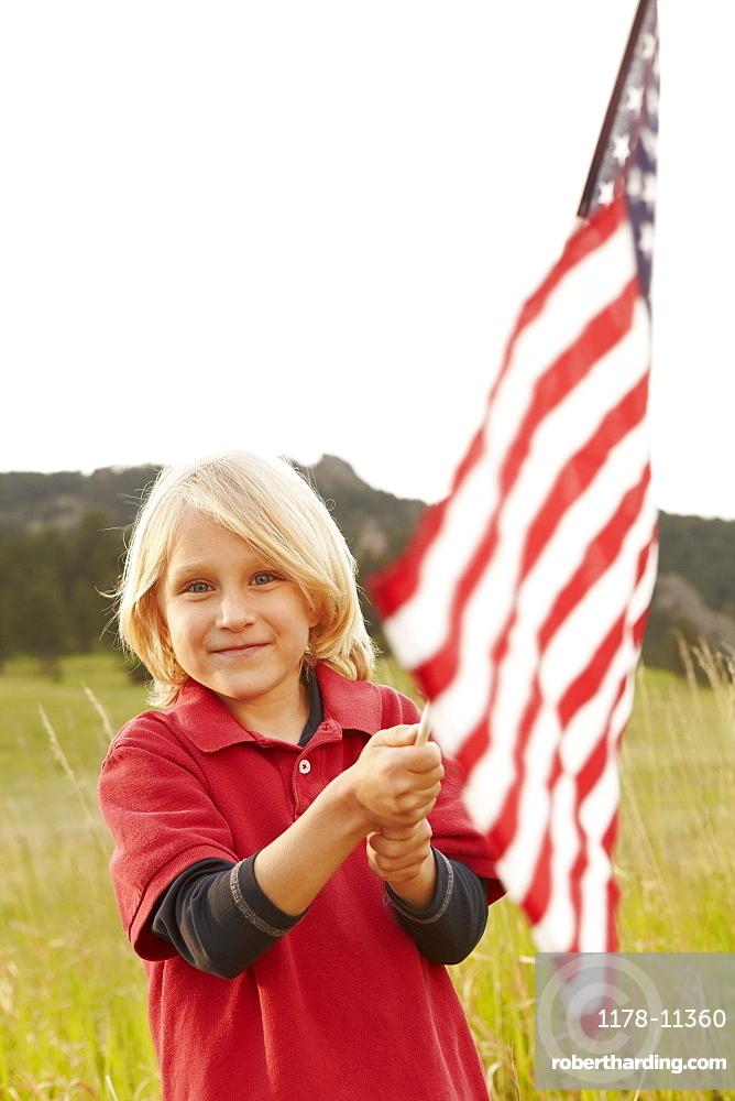 Portrait of boy (6-7) waving American flag