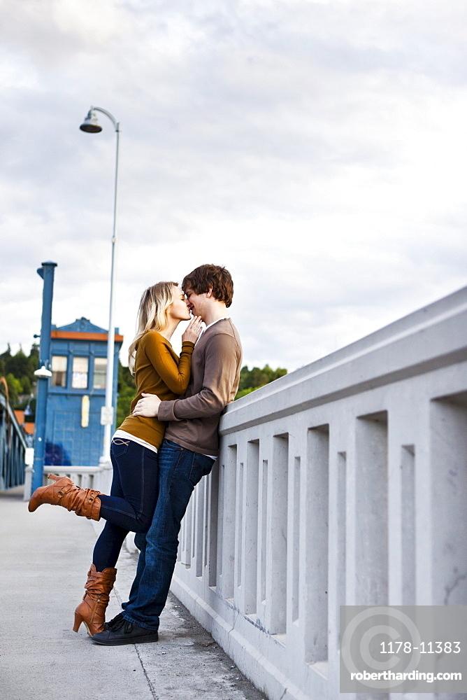 Young couple kissing on bridge