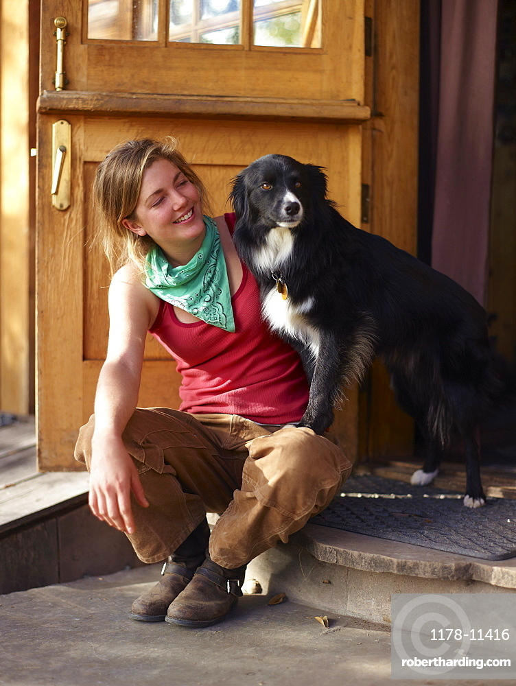 Young woman with dog sitting on porch