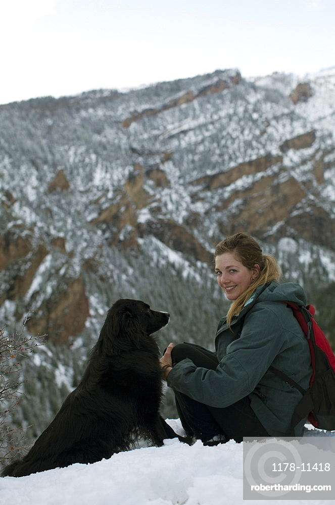 USA, Colorado, young woman and dog sitting on snowy hill