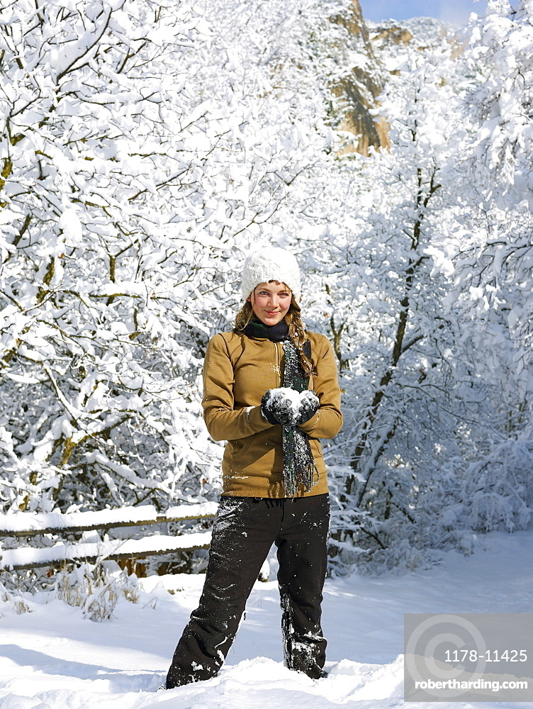 USA, Colorado, portrait of young woman making snowball