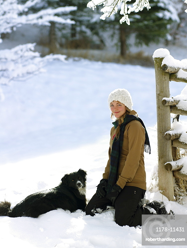 USA, Colorado, portrait of young woman with dog in snow