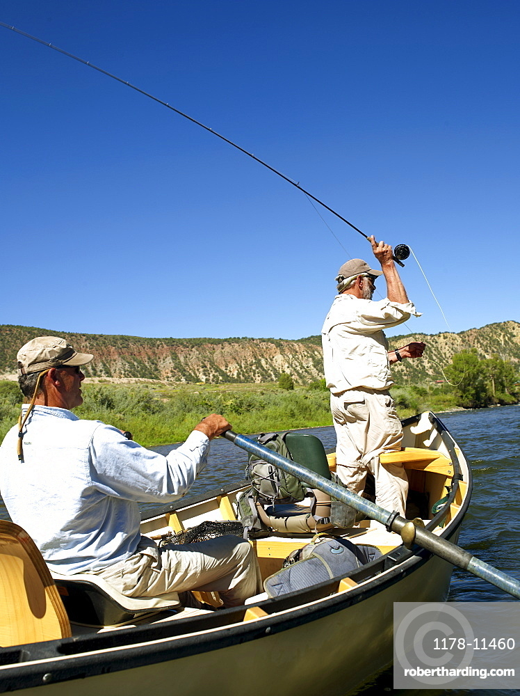 USA, Colorado, Pair of men fly-fishing on mountain river