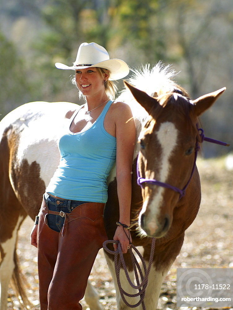 USA, Colorado, Cowgirl with horse on ranch
