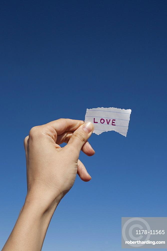 USA, Arizona, Winslow, Human hand holding love note against blue sky