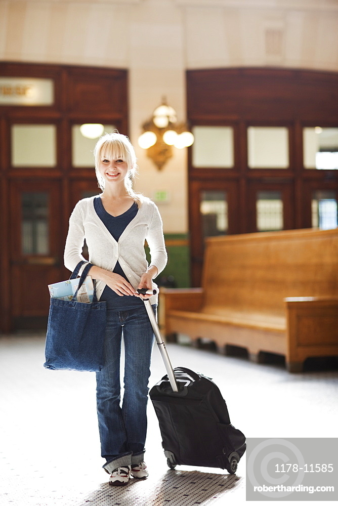 USA, Seattle, Young woman at train station standing with luggage and looking at camera