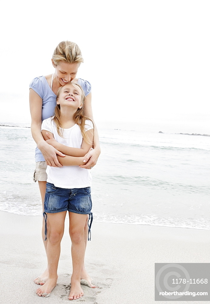 Mother with daughter (10-11) on beach