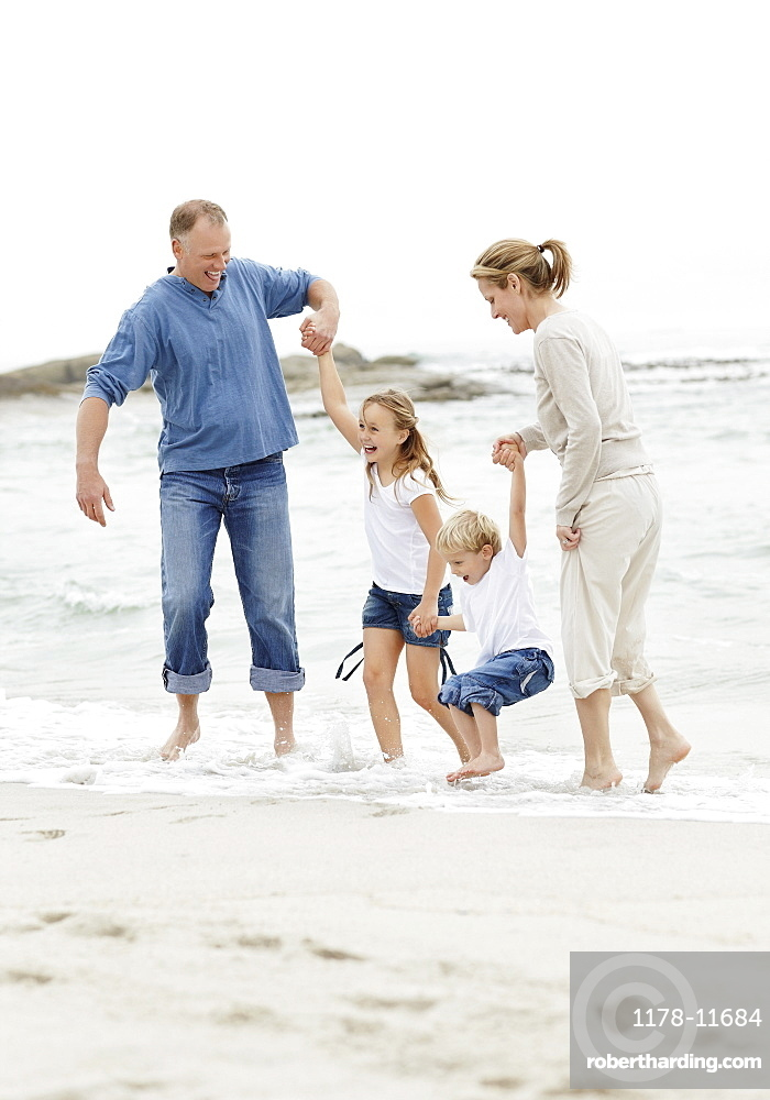 Girl (10-11) and boy (4-5) playing on beach with parents
