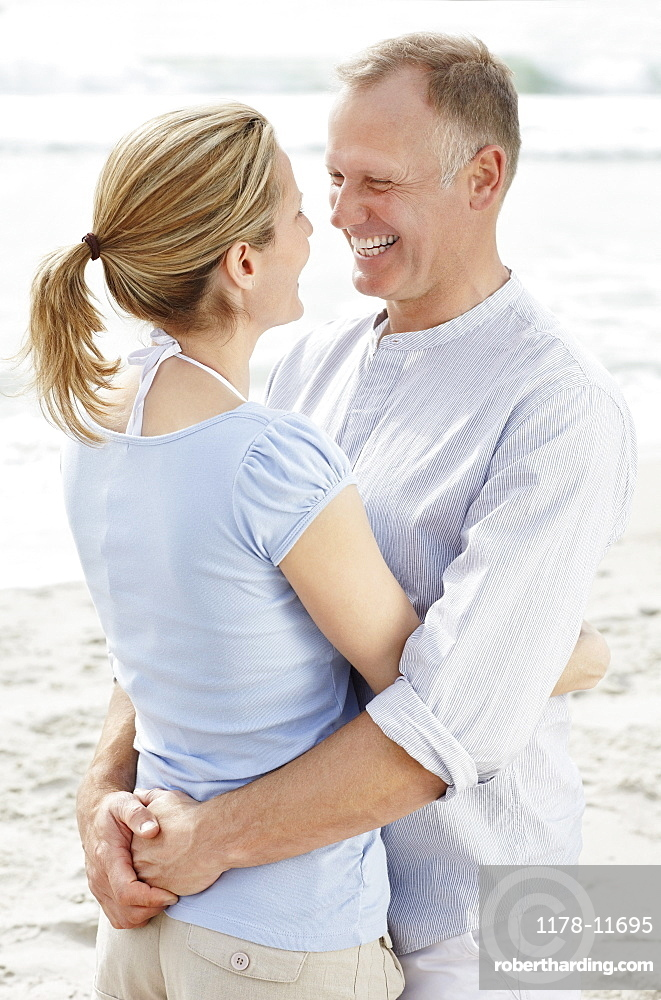 Portrait of couple embracing on beach