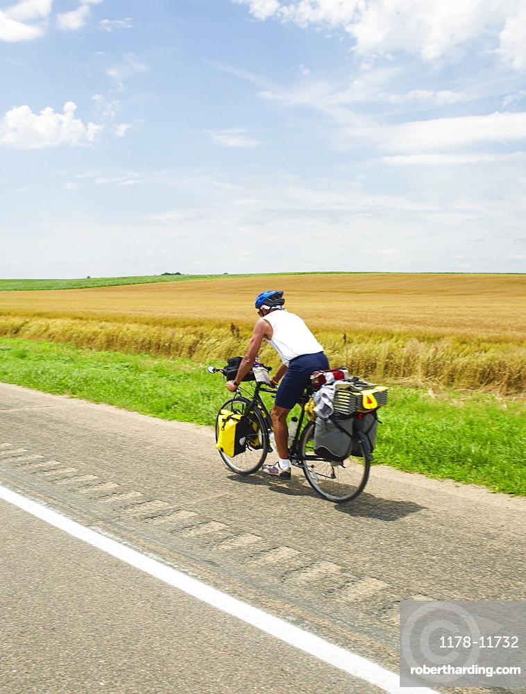 Adventure cyclist biking on rural road
