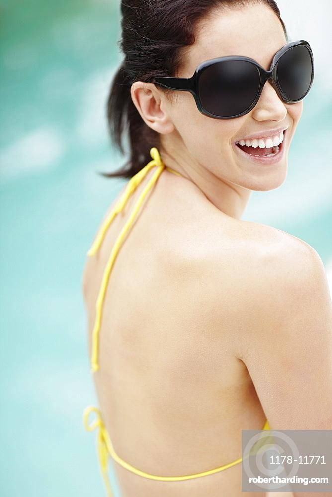 Laughing brunette wearing sunglasses and bikini