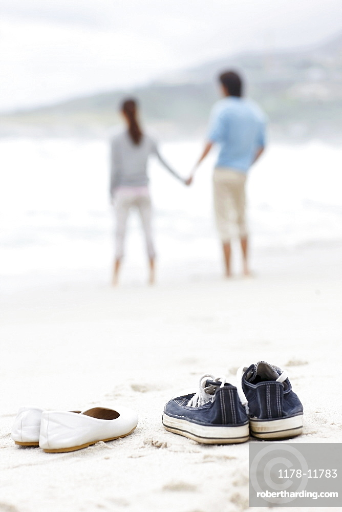 Couple walking barefoot at the beach