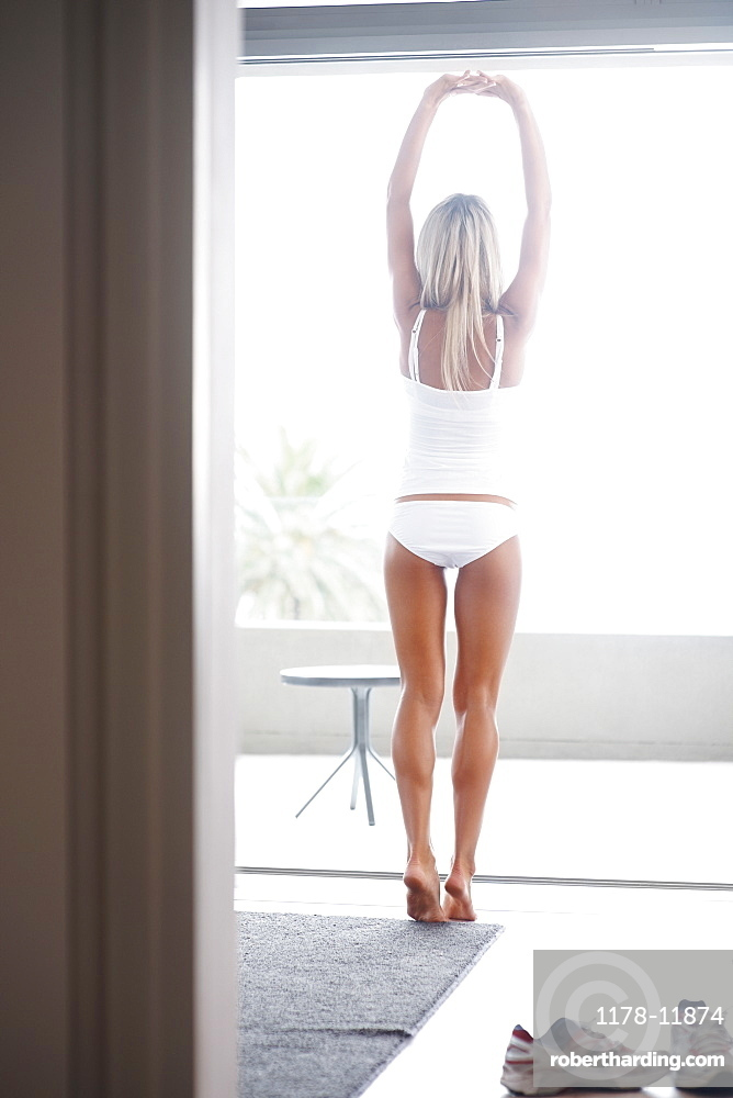 Woman wearing underwear and stretching