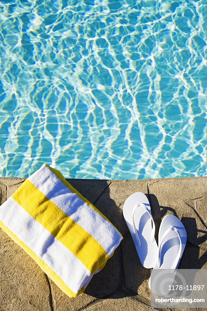 Flip flops and towel by the pool