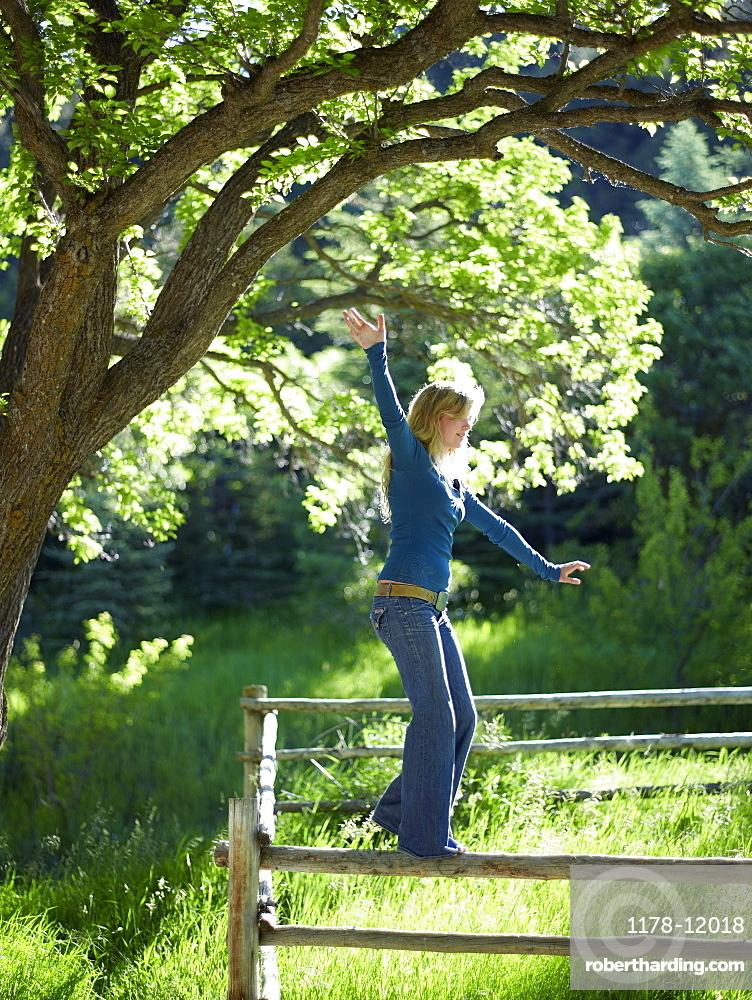 Young woman balancing on fence