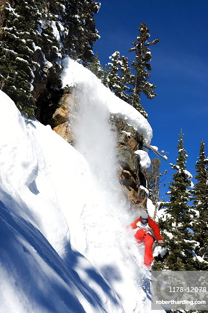 A snowboarder coming off a cliff