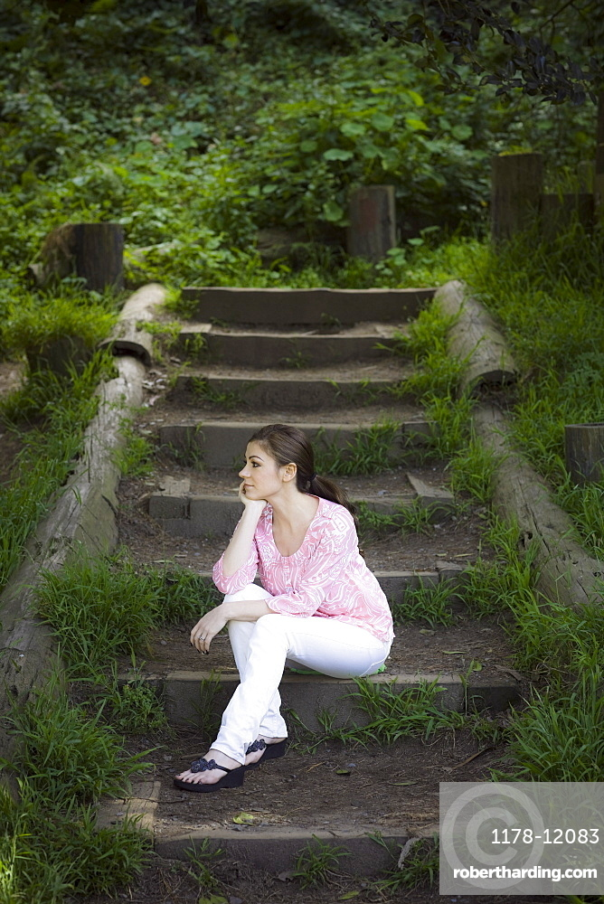 A woman sitting on a staircase outdoors