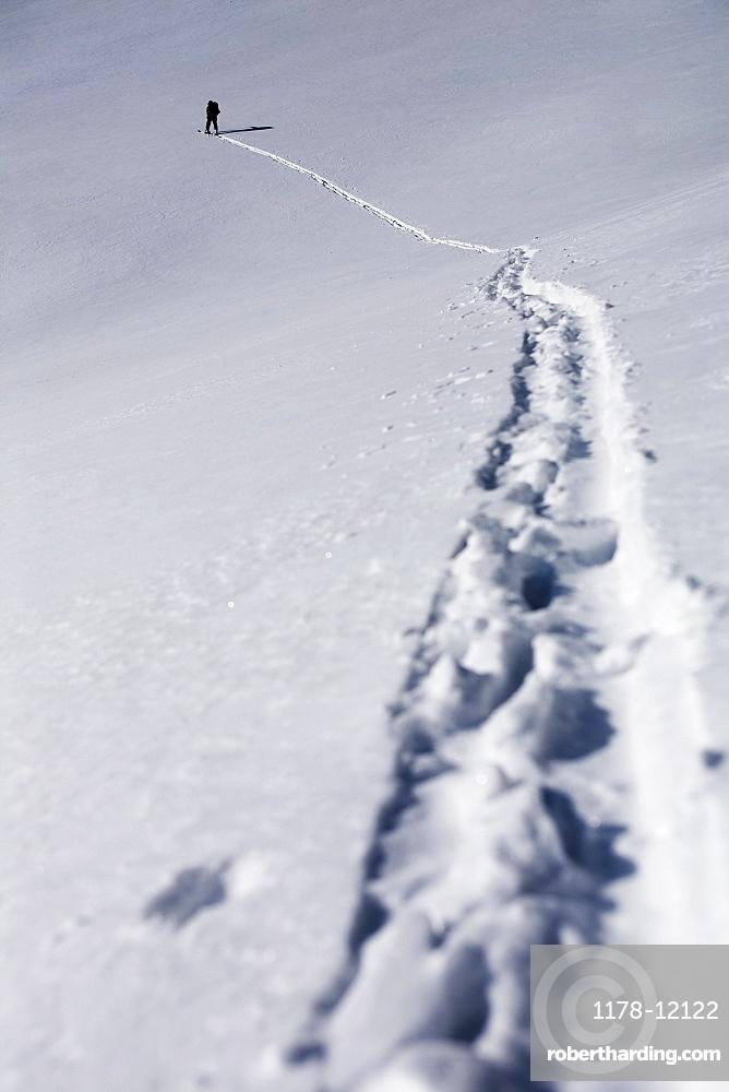 Person walking in snow up mountain, Aspen, Colorado, USA