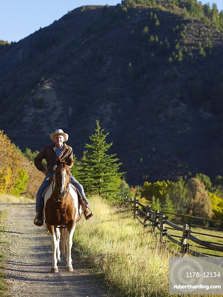 Senior man horseback riding, Colorado, USA