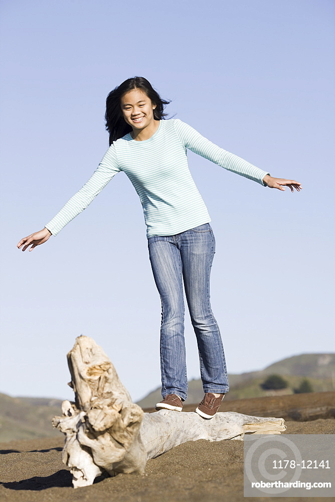 Teenage girl balancing on driftwood