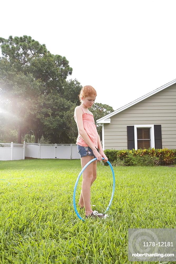 Girl standing in backyard with hula hoop