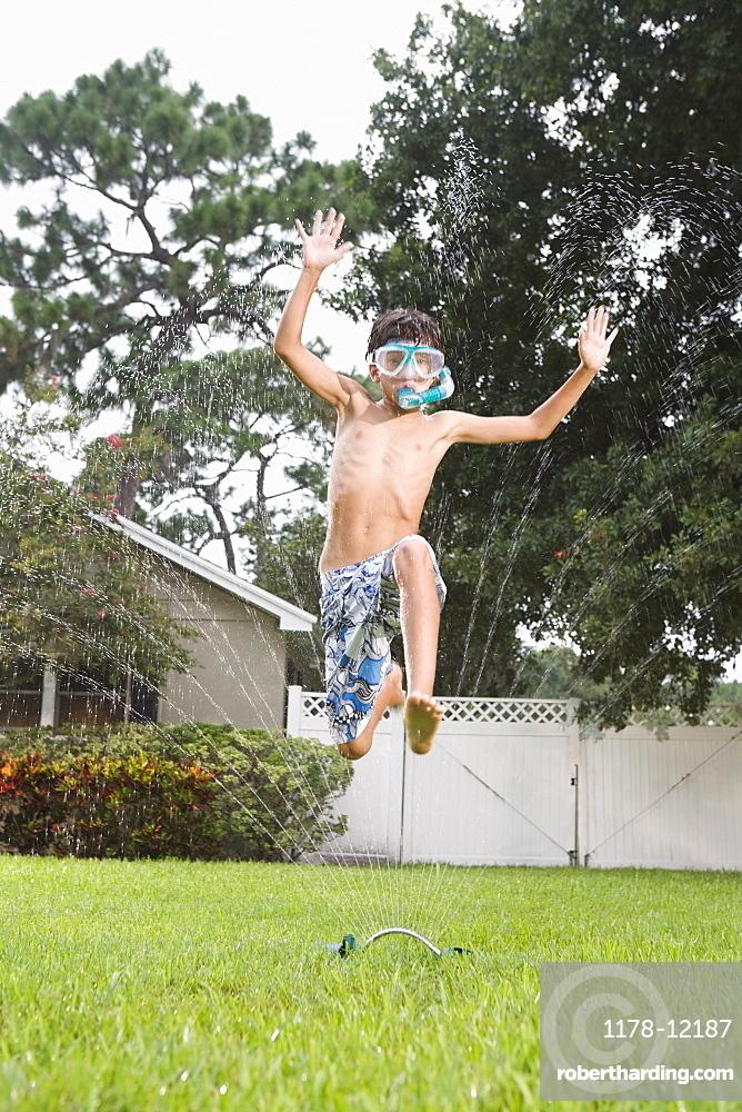 Boy with snorkeling mask running through sprinkler