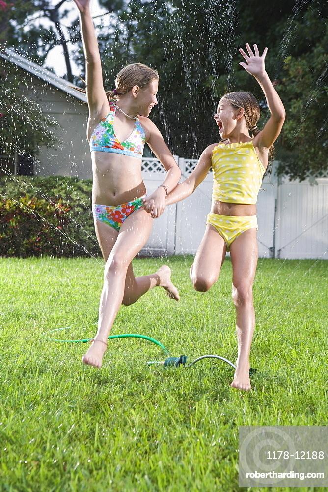 Sisters in bathing suits running through sprinkler
