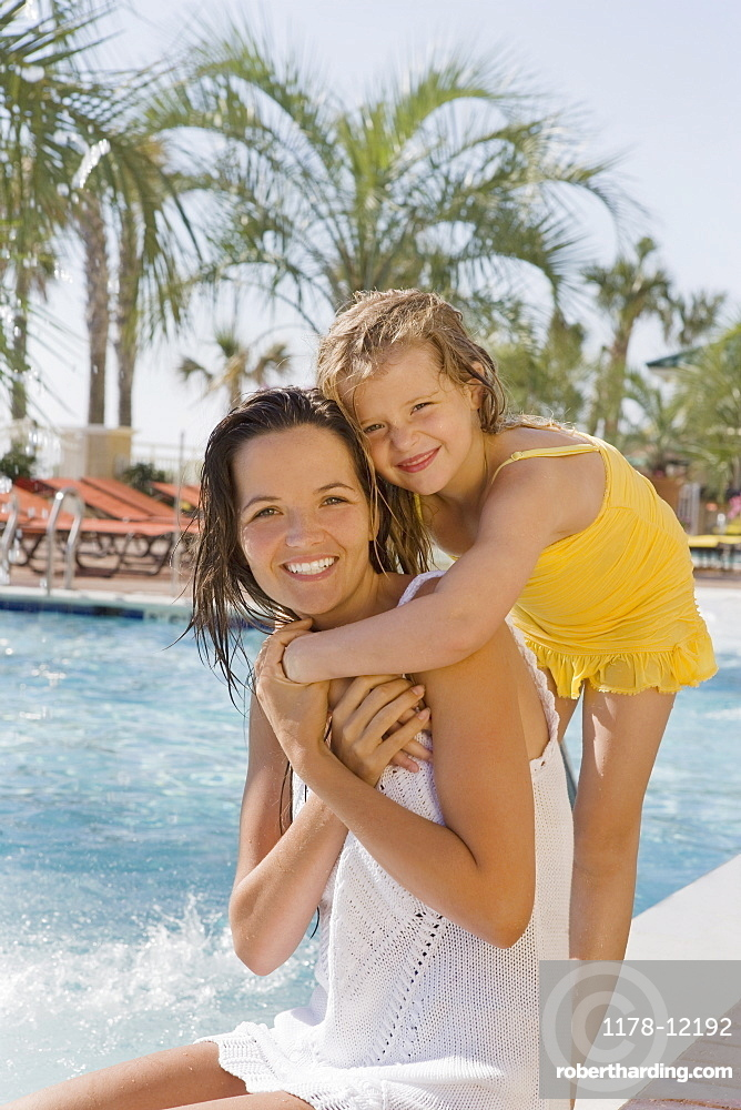 Portrait of mother and daughter hugging at poolside