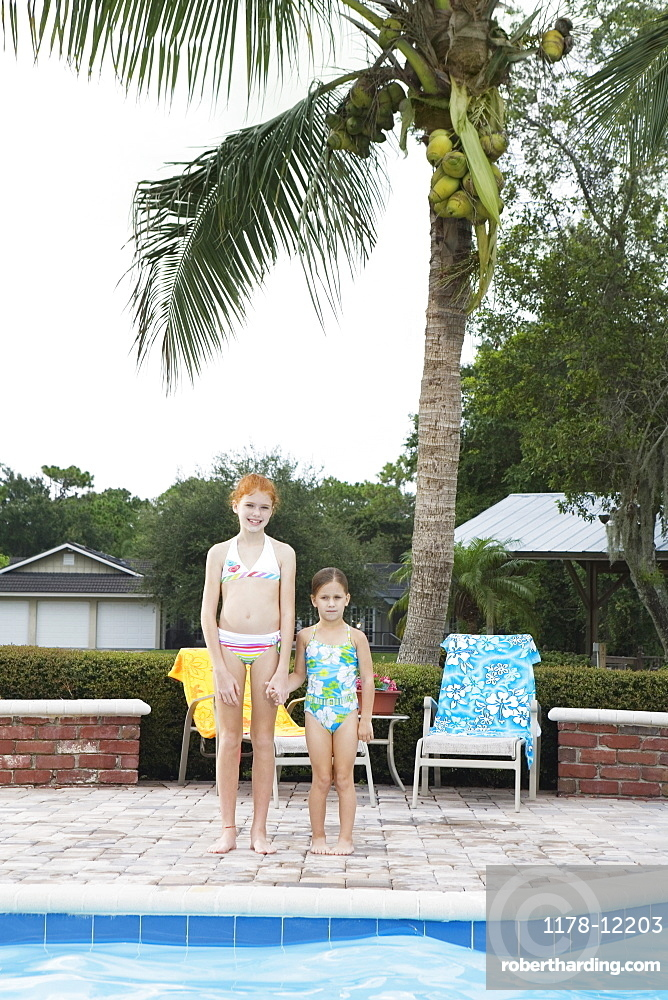 Girls standing at edge of swimming pool