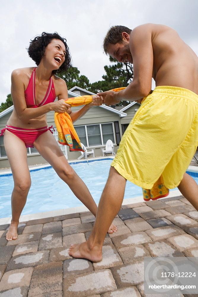 Couple playing tug-of-war with towel
