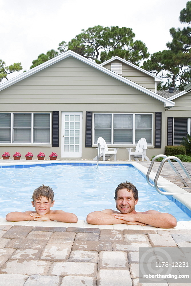 Father and son leaning on edge of swimming pool