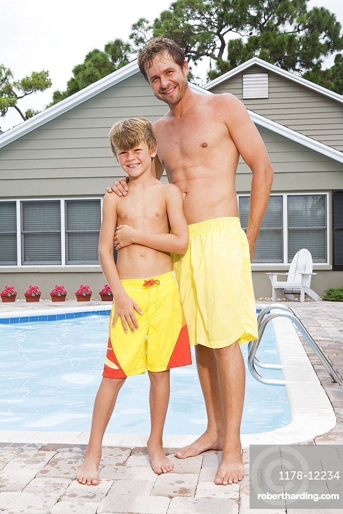 Father and son posing by swimming pool