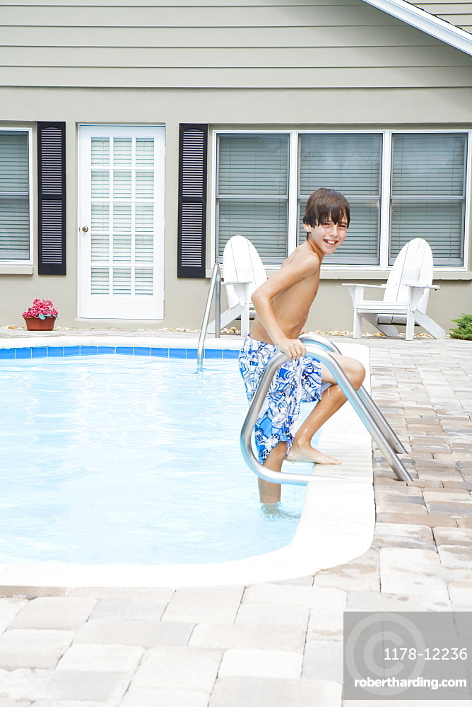 Boy stepping out of swimming pool