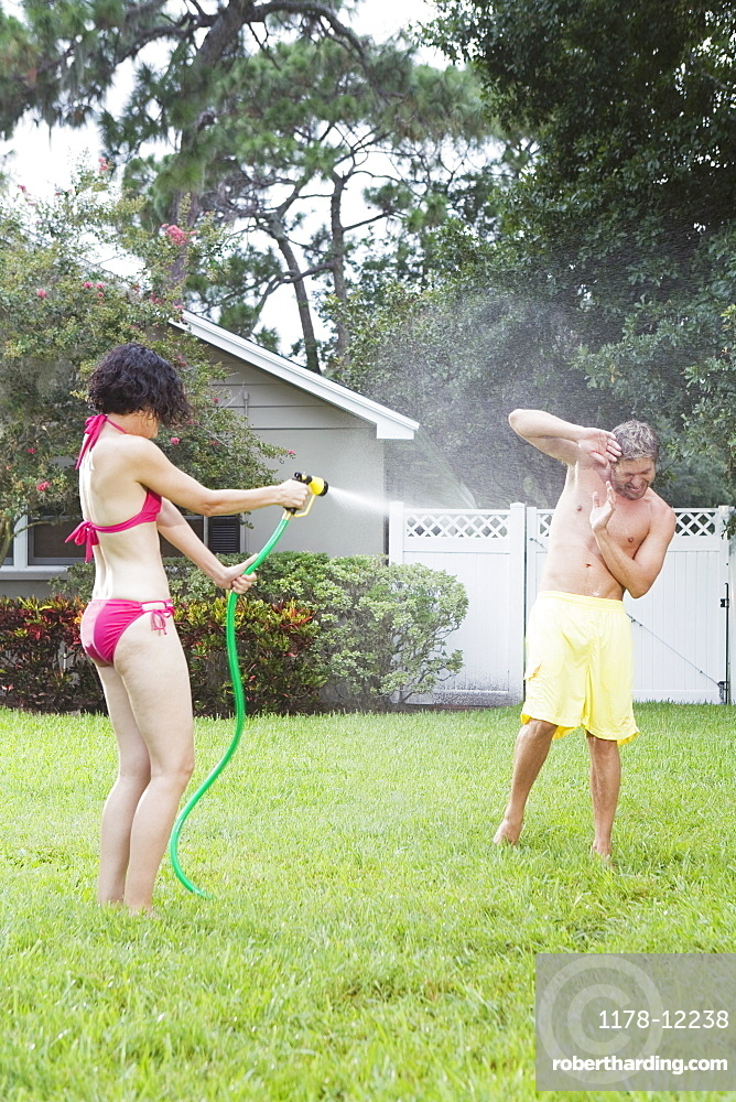 Woman spraying man with hose in backyard