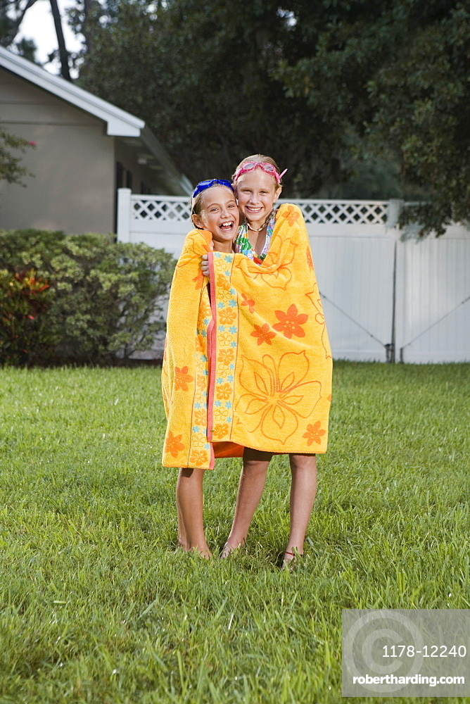 Girls wrapped in towels on lawn